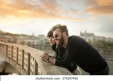 Full beard man with beautiful woman have fun in the city. Stylish couple enjoying beautiful sunset in the city from the the bridge. Blurred background with Prague castle. Color toned image.