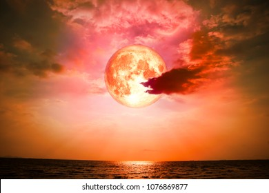 full blood moon back silhouette cloud on the horizonal line in sea and colorful sky