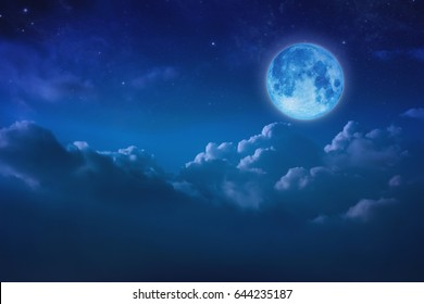 Full blue moon behind cloud over sky and star at night. lunar shine moonlight over cloudy with copy space background for headline text or graphic design. Elements of this image furnished by NASA