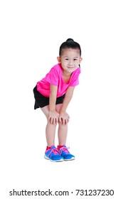 Voller Körper eines süßen asiatischen Kindes in Sportbekleidung, lächelnd und mit Händen auf den Knien stehend. Gesundes chinesisches Mädchen entspannt sich im Studio. Sport und aktiver Lebensstil. Einzeln auf weißem Hintergrund.