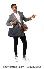Full body of African american business man traveling with suitcases pointing finger to the side and presenting a product while smiling on white background