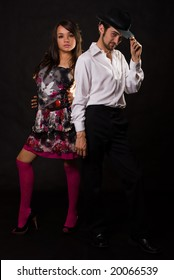 Full body of an attractive Caucasian couple wearing dancing attire standing over black