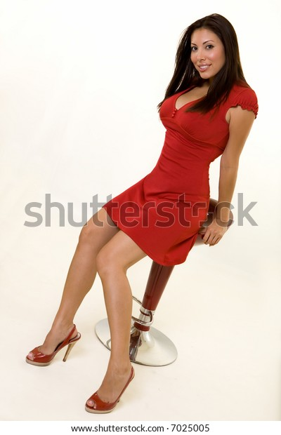 Full body of an attractive long haired brunette Hispanic woman wearing a red dress and matching shoes sitting on a red stool