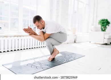 Full body barefoot concentrated male in sportswear standing in Eagle Crunch pose on mat while practicing yoga and balancing on leg