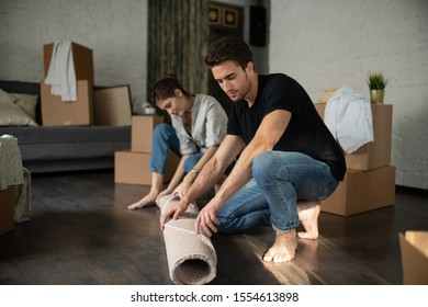 Full body barefoot man and woman unrolling soft carpet on floor in modern apartment while moving into new place