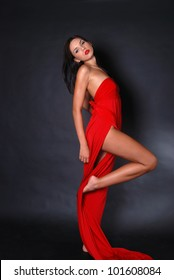 Full body of a beautiful woman wearing red dress on black background