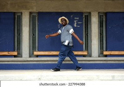 Full body of a black South African adult young man in casual clothes walking outside in front of a building.