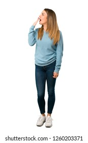 Full body of Blonde woman with blue shirt yawning and covering wide open mouth with hand on white background