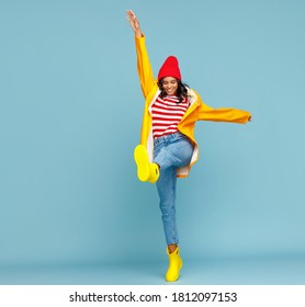 Full body cheerful ethnic woman in raincoat and boots smiling and kicking air on autumn day against blue background