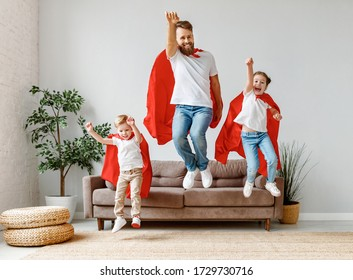 Full body of cheerful father with two children in casual clothes and red superhero cloaks jumping from couch to floor while playing heroes at home