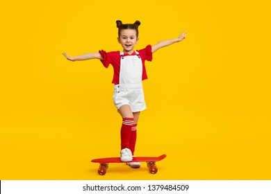 Full body cheerful little child in trendy outfit  stretching out arms and and stepping on modern skateboard against yellow background