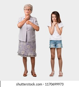 Full body of an elderly lady and her granddaughter with a sore throat, sick due to a virus, tired and overwhelmed