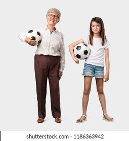 Full body of an elderly lady and her granddaughter smiling and happy, holding a soccer ball, competitive attitude, excited to play a game