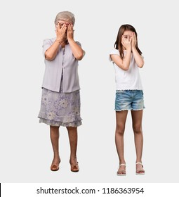 Full body of an elderly lady and her granddaughter feels worried and scared, looking and covering face, concept of fear and anxiety