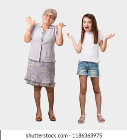 Full body of an elderly lady and her granddaughter crazy and desperate, screaming out of control, funny lunatic expressing freedom and wild