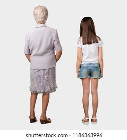 Full body of an elderly lady and her granddaughter showing back, posing and waiting, looking back