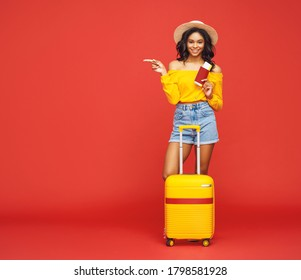 Full body ethnic woman with tickets and suitcase smiling and pointing away during summer trip against red backdrop