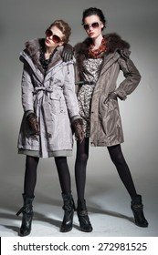 Full body fashion model in fur coat clothes posing-gray background