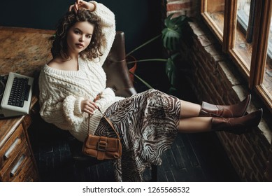 Full body fashion portrait of young beautiful confident woman wearing cozy white knitted sweater, animal print skirt, cowboy style boots, holding small brown bag, posing at loft interior
