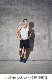 Full body fitness portrait of muscular man, standing with both hands on his waist looking away