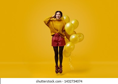 Full body freakish young lady in colorful outfit holding bunch of vivid balloons and saluting while jumping against yellow background