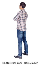 Full body half turn back view portrait of smiling young man with crossed arms on his chest wearing metal frame glasses, checkered shirt, blue jeans and black shoes isolated on white background