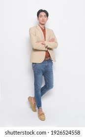 Full body handsome young man in suit with jeans posing with arms crossed on white background