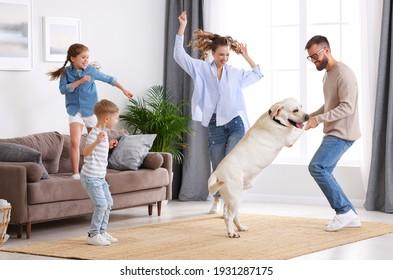Voller Körper der glücklichen, spielerischen Familie: Eltern und kleine Kinder mit süßem, reinrassigen Labrador Retriever Hund, der Spaß hat und zusammen im Wohnzimmer tanzt