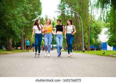 Full body happy women in blue jeans walking in summer park, outdoors
