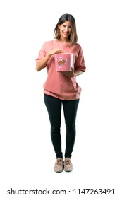 Full body of  Happy Young girl with pink shirt eating popcorns