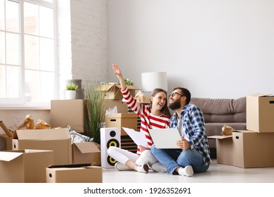 Full body of happy young man with laptop on knees  sitting with wife pointing up while among packed stuff and discussing ideas about interior design of new home