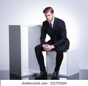 Full body image of a handsome young business man sitting on a white cube holding his hand together, looking at the camera.