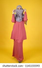 Full body image of Muslim women with yellow background. Studio shot