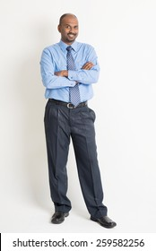 Full body Indian businessman arms crossed standing on plain background with shadow