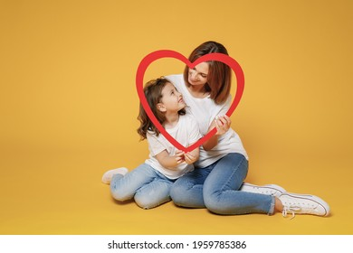 Full body length happy woman in basic white t-shirt have fun sit on floor child baby girl 5-6 years old Mom mum little kid daughter isolated on yellow color background studio Mother's Day love family
