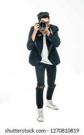 Full body length portrait indian man taking photo with dslr camera looking at camera isolated over white studio background.