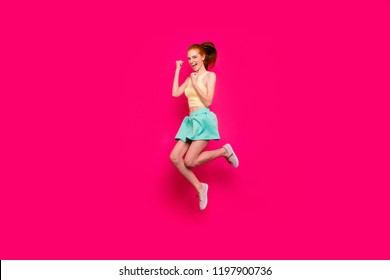 Full body length size of attractive positive playful glad red-haired girl in tanktop and short skirt with ponytail, winning gesture, jumping up in air, isolated over bright vivid fuchsia background