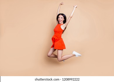 Full body length size photo portrait of mad cheerful ecstatic rejoicing delightful glad shouting lady in shoes sneakers jumping up raising hands isolated pastel beige background