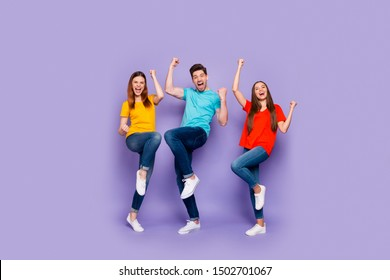 Full body length size photo of cheerful excited ecstatic positive lucky company of fellows having fun raising fists up isolated over violet background