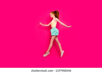 Full body length size, profile side view of attractive charming positive dreamy red-haired girl in tanktop and short skirt with ponytail, strolling in air, isolated on bright vivid fuchsia background