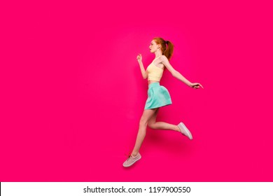Full body length size, profile side view of nice adorable charming positive dreamy red-haired girl in tanktop and short skirt with ponytail, running in air, isolated on bright vivid fuchsia background