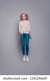 Full body length size vertical portrait of attractive beautiful curly-haired blonde caucasian young girl wearing casual shirt and jeans flying in air. Isolated over grey background