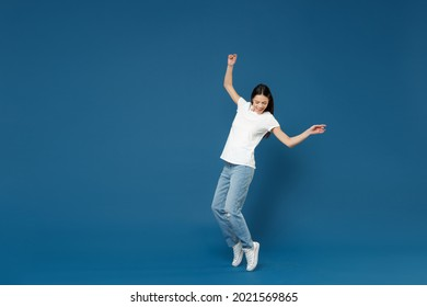 Full body length young latin woman 20s in white casual basic t-shirt keep hands outstretched leaning back look aside standing on toes dancing have fun isolated on dark blue background studio portrait
