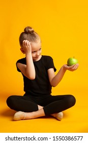Full body little girl in leotard scratching head and looking at green apple while sitting against yellow background during break in training