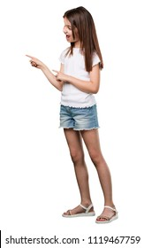 Full body little girl pointing to the side, smiling surprised presenting something, natural and casual