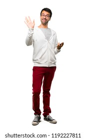 Full body of Man with glasses and listening music saluting with hand with happy expression on white background