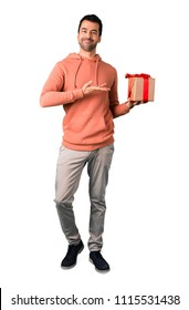 Full body of Man in a pink sweatshirt holding gift boxes in hands on isolated white background