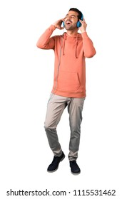 Full body of Man in a pink sweatshirt listening the favorite song with headphones and dancing on isolated white background