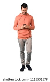 Full body of Man in a pink sweatshirt sending a message or email with the mobile on isolated white background. Ideal for use in architectural designs