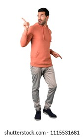 Full body of Man in a pink sweatshirt enjoy dancing while listening to music at a party on isolated white background